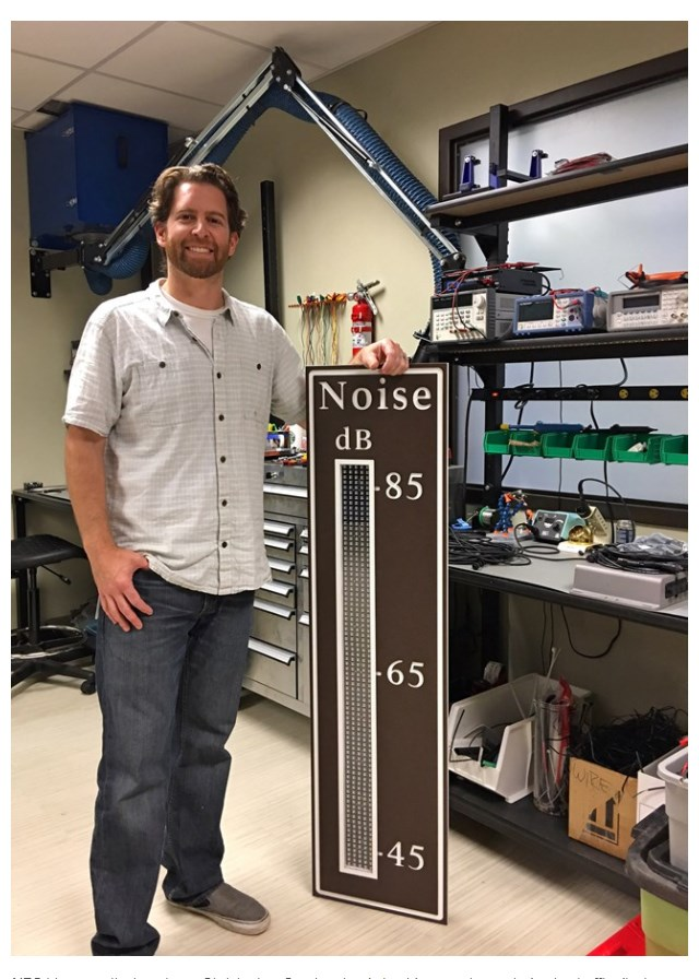 NPS bio-acoustical engineer Christopher Garsha stands beside a newly created noise traffic display sign.