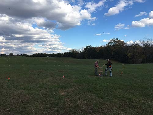 Two people use archeological investigation tools in open field.
