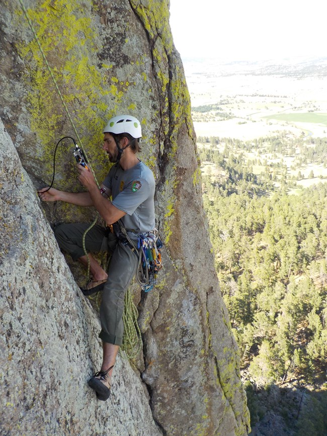 A properly equipped climber using a device to look into a crack on Devils Tower