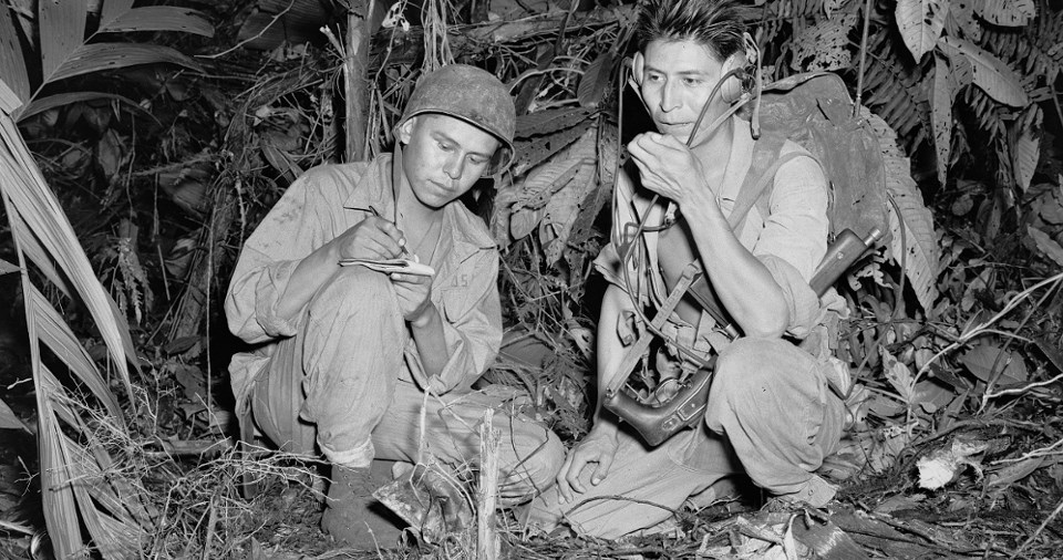 Two military men crouch in the jungle in World War II