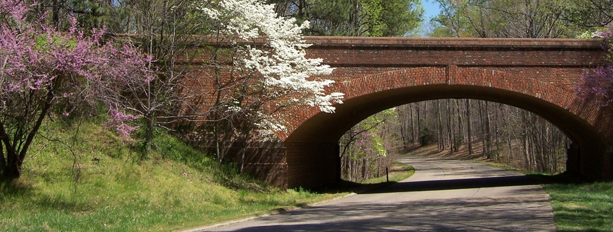 The colonial Parkway in spring time winding under an arched brick bridge