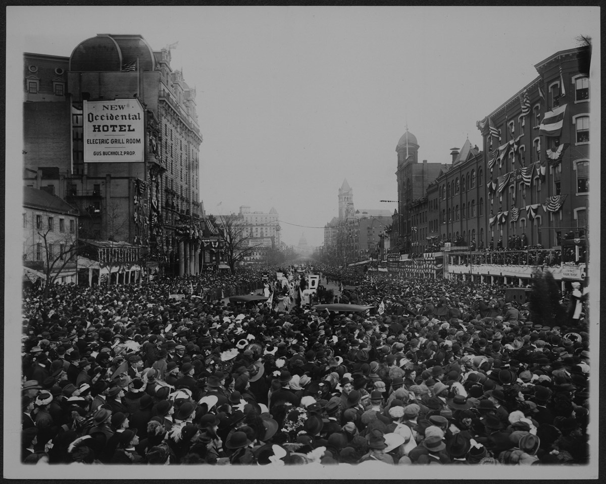 Photograph of suffrage procession surrounded by huge crowds in the street.