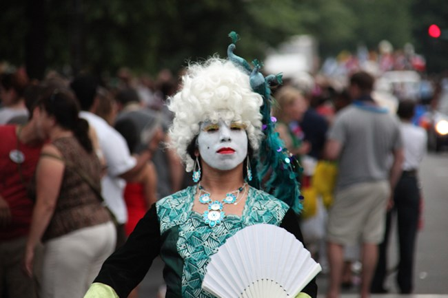 A person with white face, white wig, and opulent blue-green gown