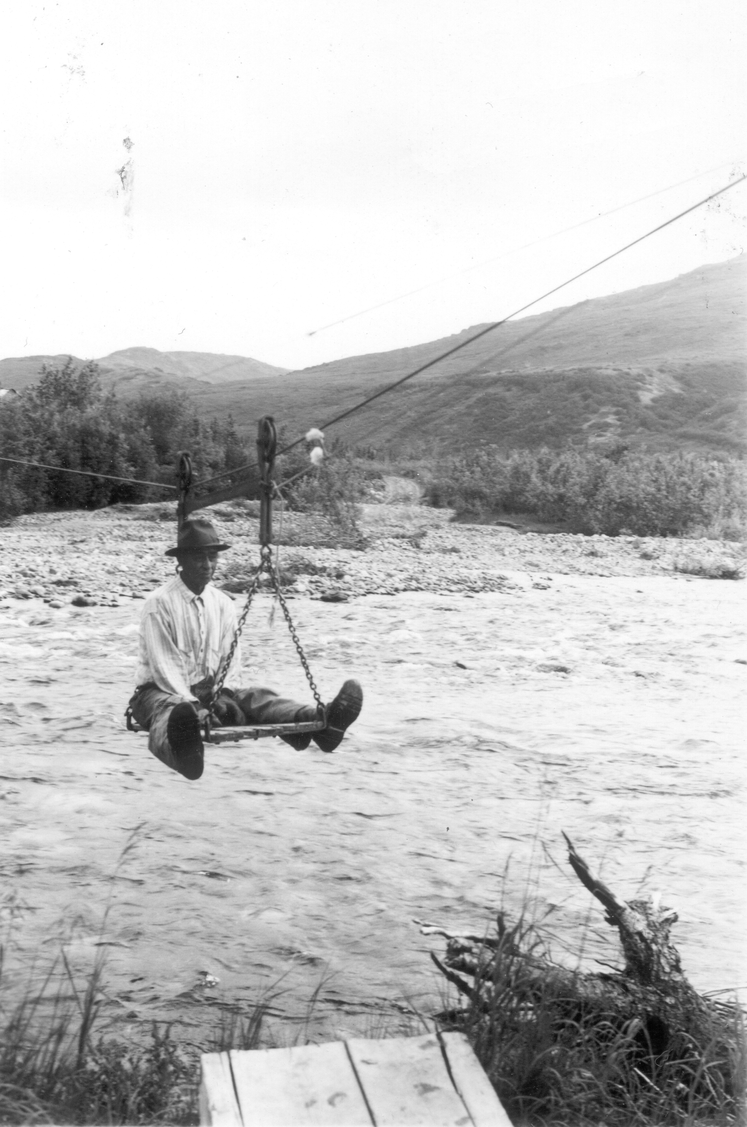 man riding on a tramway over a creek