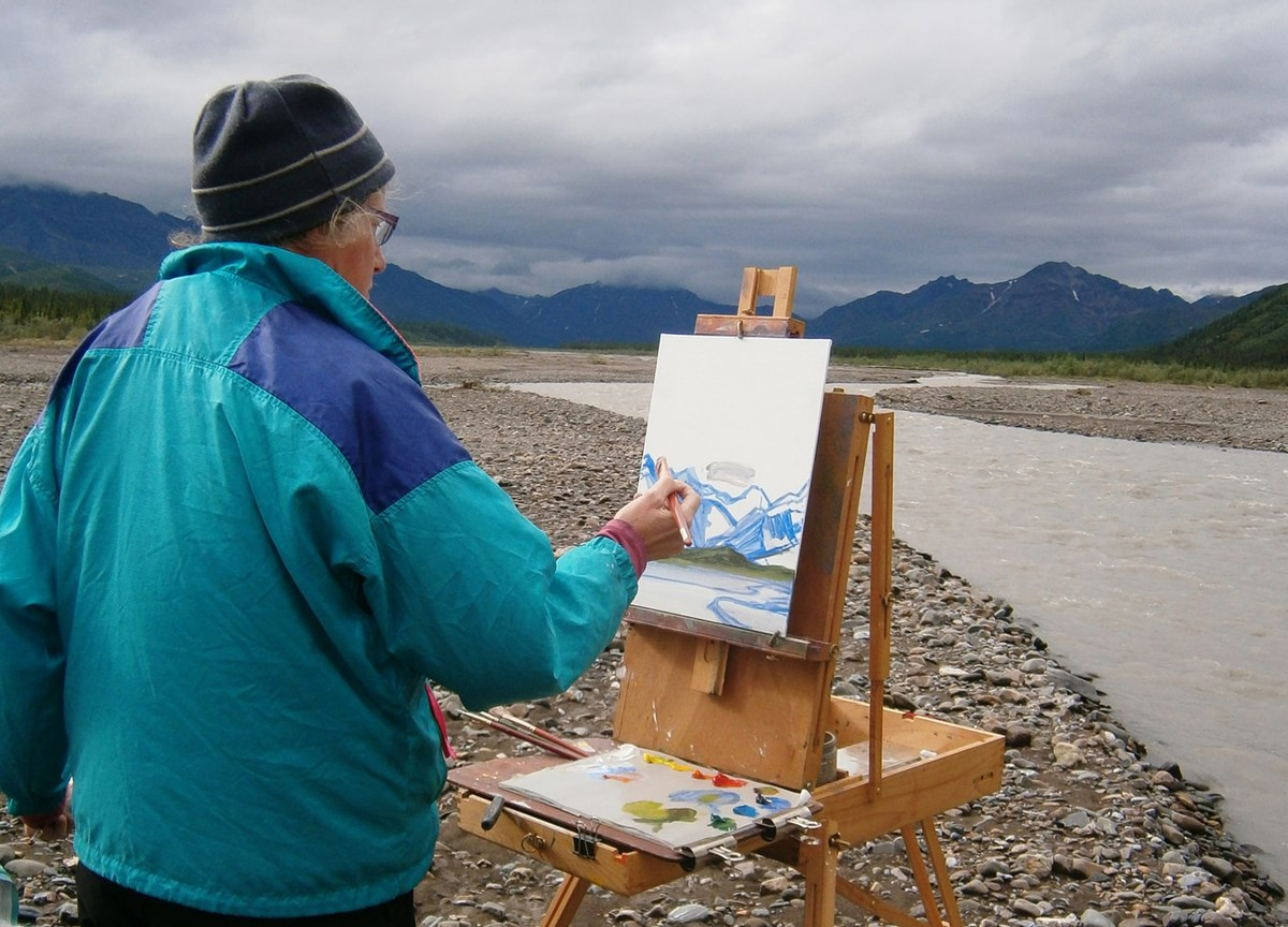 Man painting a canvas on an easel along a shoreline.