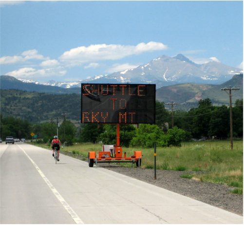 a dynamic message board sign along the side of a road, mountain in distance