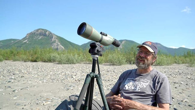 A researcher observing birds through spotting scope.