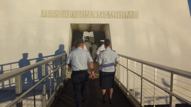 People in military uniforms walk up a ramp to enter the USS Arizona Memorial.