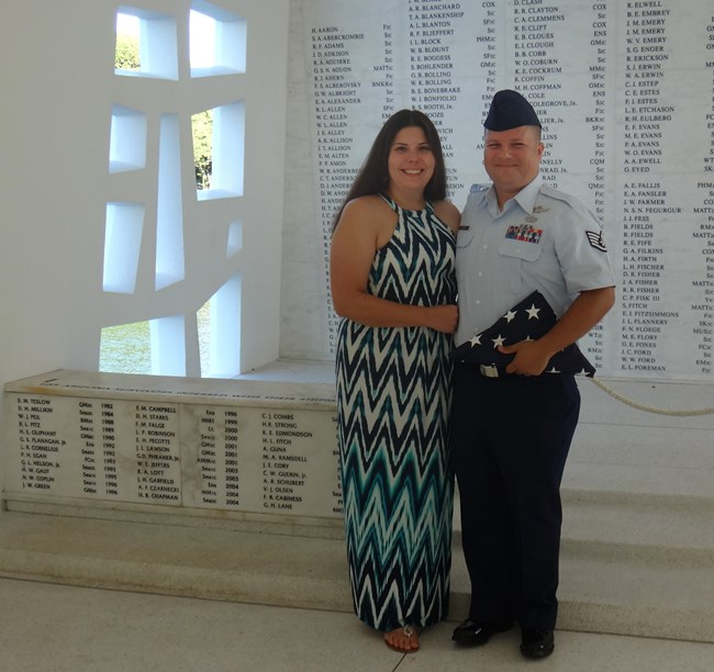 Woman in dress locks arms with a man in Air Force uniform holding a folded flag. They stand in front of the USS Arizona Memorial wall.