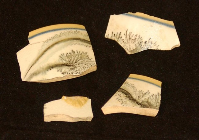 Four ceramic fragments with yellow and blue borders and a black mochaware decoration on a white band in the center.