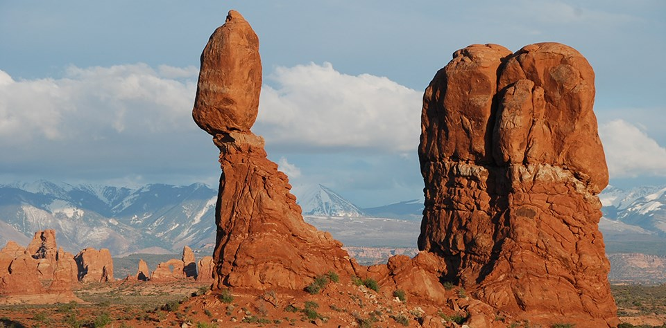 a tall balanced rock with a distant arch and snow-capped mountains in the background