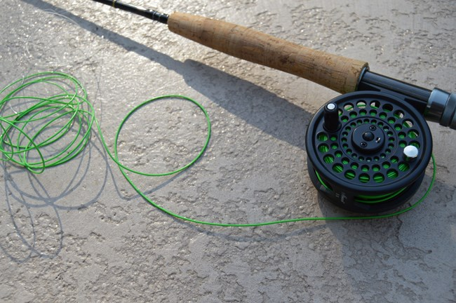 close up of fly fishing rod, reel, and line on cement
