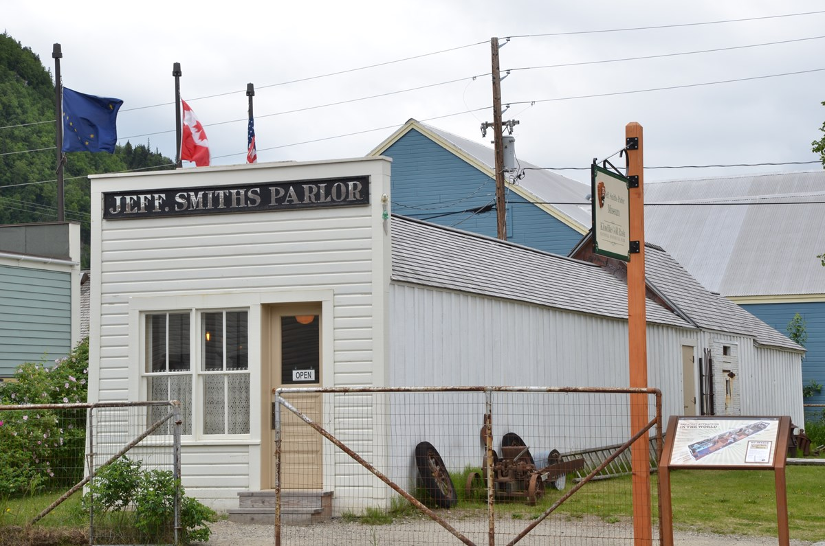 "White building with sign ""Jeff Smiths Parlor"" written above."
