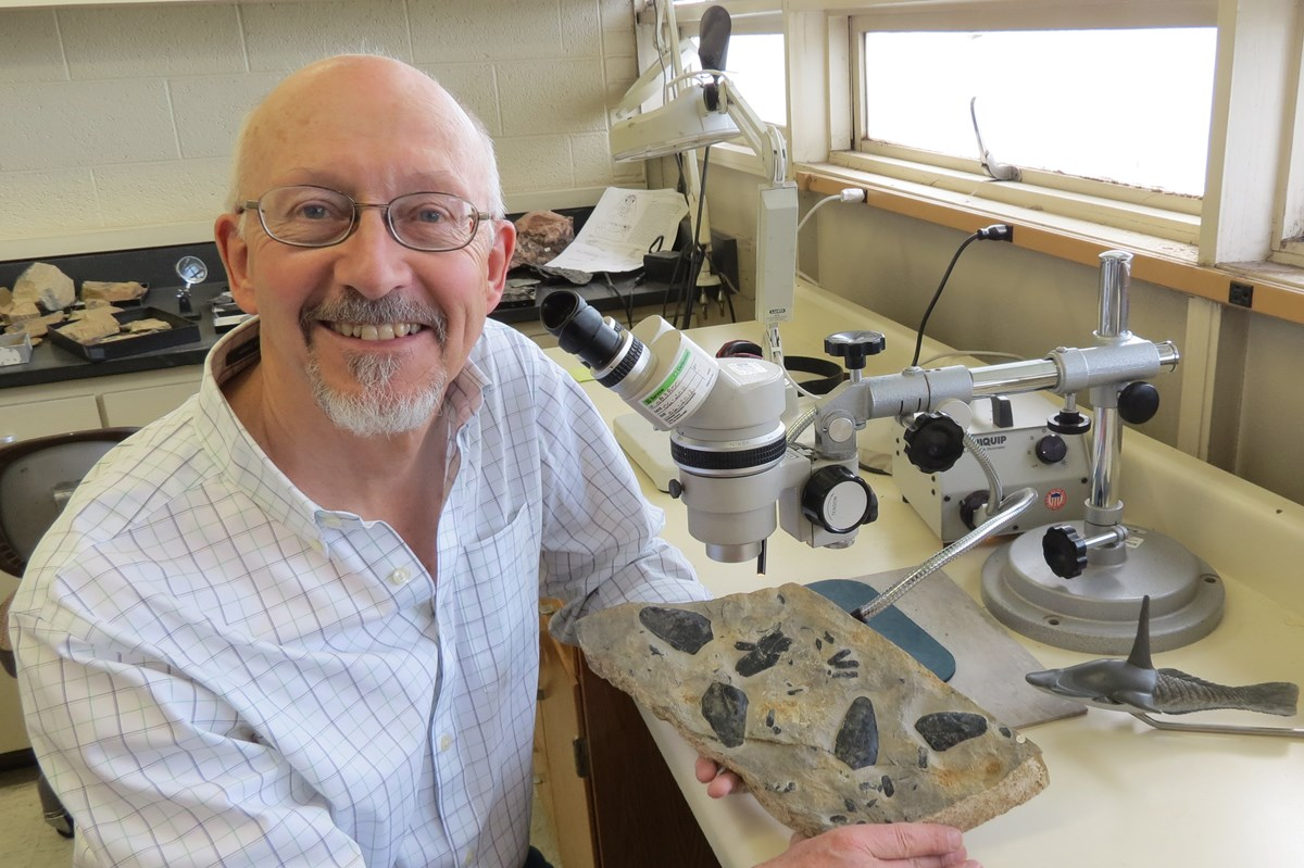 Paleontologist David Elliott at his microscope with some fossil heterostracans