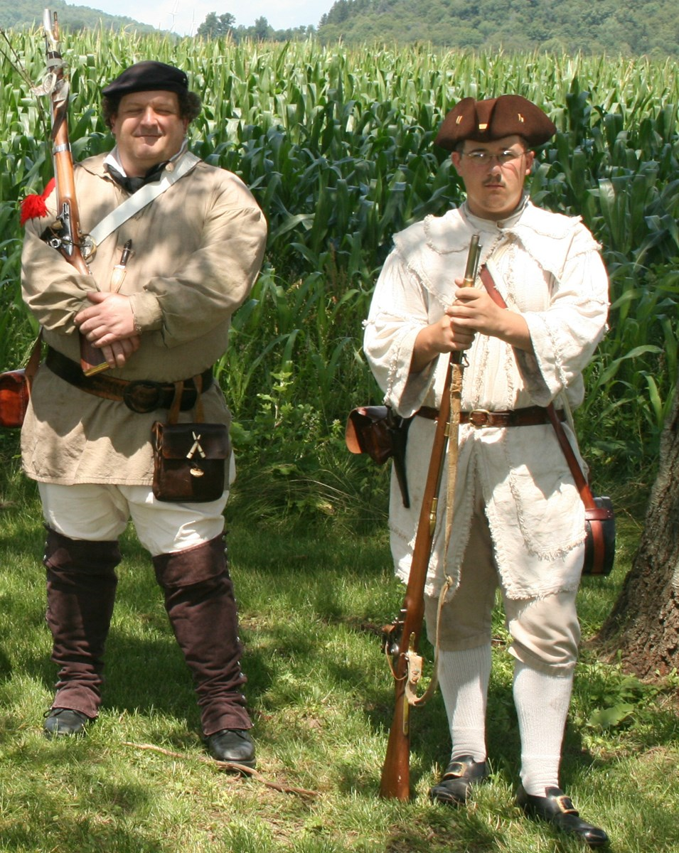 2 people in Continental Soldier uniforms stand with muskets ready under green trees.
