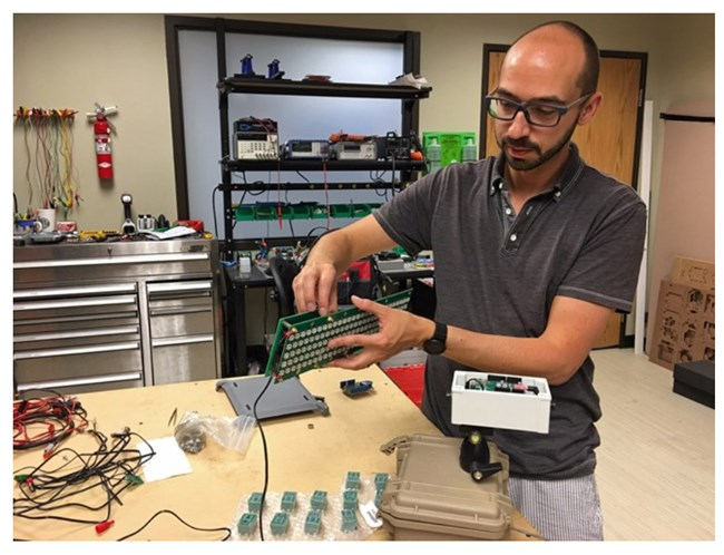 NPS physical scientist Damon Joyce shows some of the electronic components that comprise the noise level display signs.