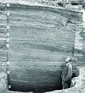 Man stands in front of rock wall showing many layers of occupation at Onion Portage excavation site (1960s).