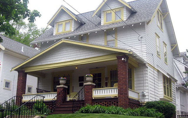 White house with yellow trim and a large front porch.