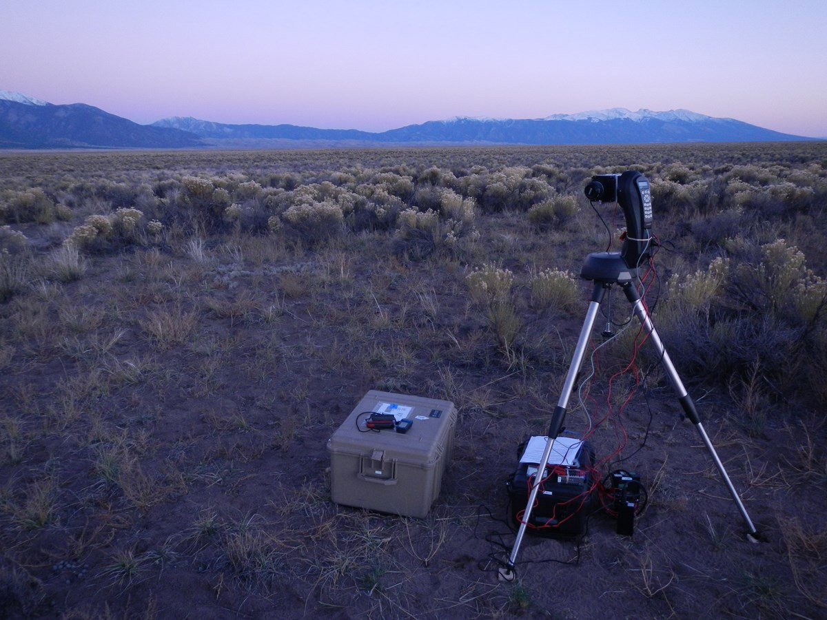 The night sky CCD camera is installed in a high desert prairie location with snow-capped mountains beyond.