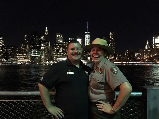 Nighttime scene of a man in blue shirt with park ranger spouse with New York City in background.