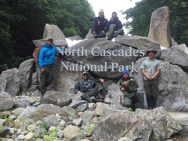 Group posing for a photo at an entry sign for North Cascades National Park