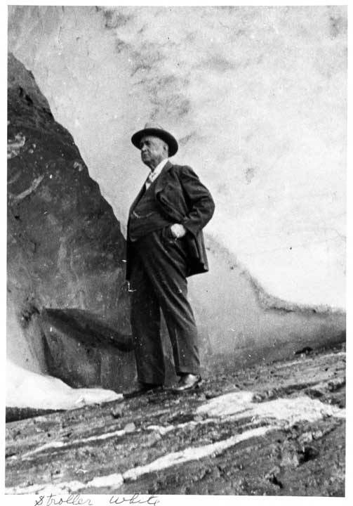 An older man in a suit stands upon a glacier.