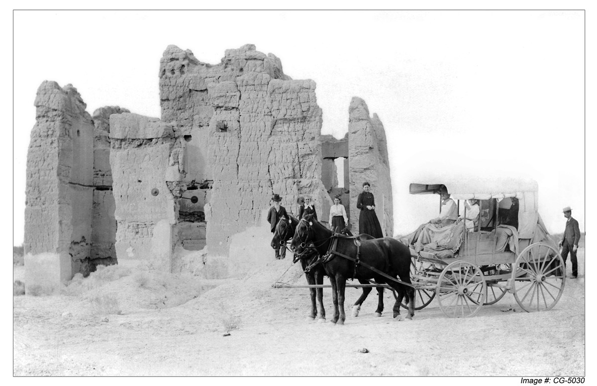 Historic black and white photo of visitors in a horse drawn carriage at abode ruins