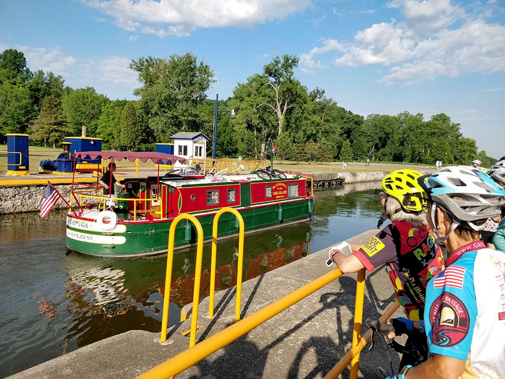 Cyclists stop to look at a boat in the canal.