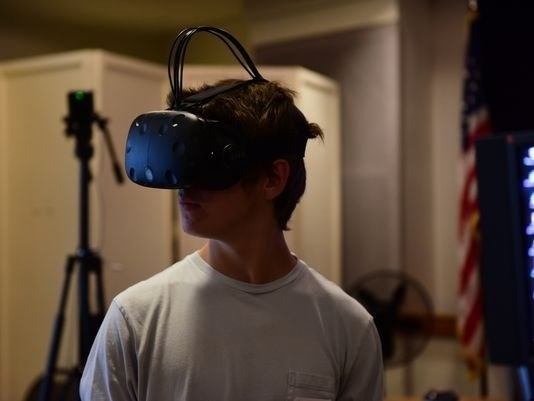 Young man wears virtual reality glasses.