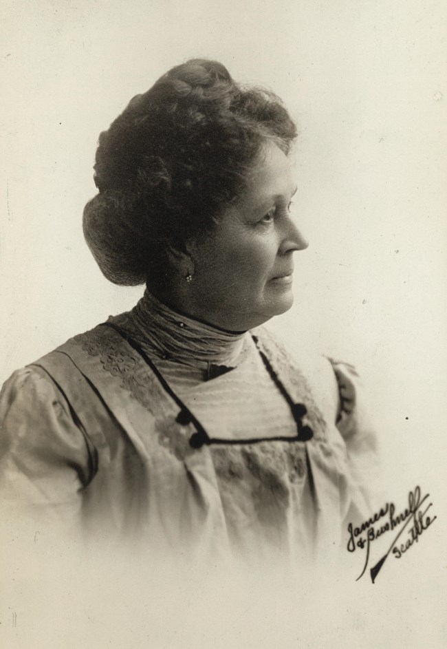 Formal portrait, head and shoulders, Emma Smith Devoe of Seattle, Washington, facing front with head turned in profile to right, wearing high-neck collar.