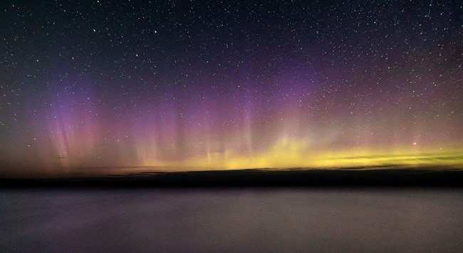 Northern Lights shinning across the lakes in shades of yellow and purple