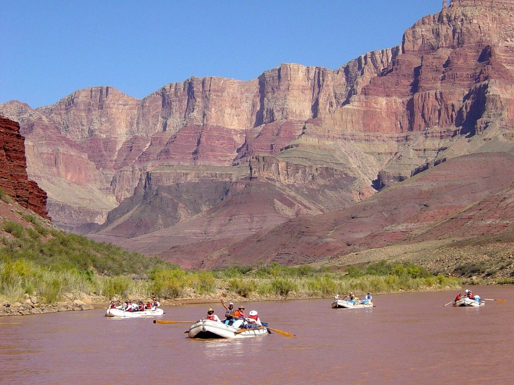 4 rafts floating down river with canyon wall in background.