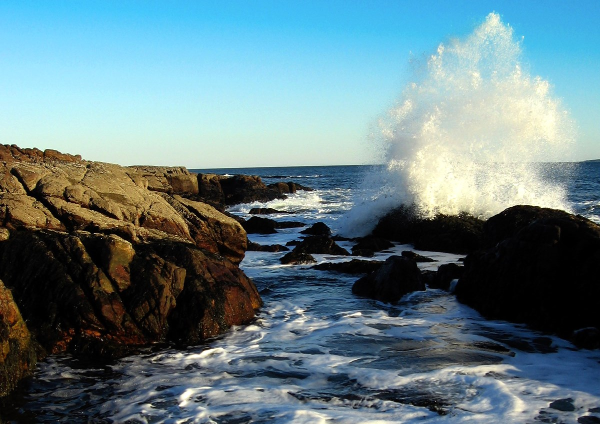 A wave crashes against the shore at Acadia National Park