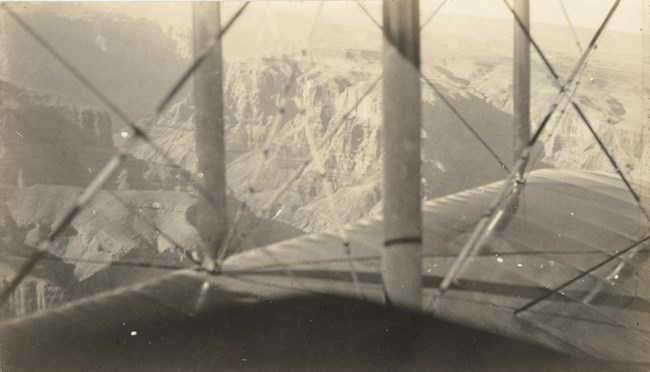 Black and white photo looking out over the wing of a biplane. Beyond is a view of the Grand Canyon.