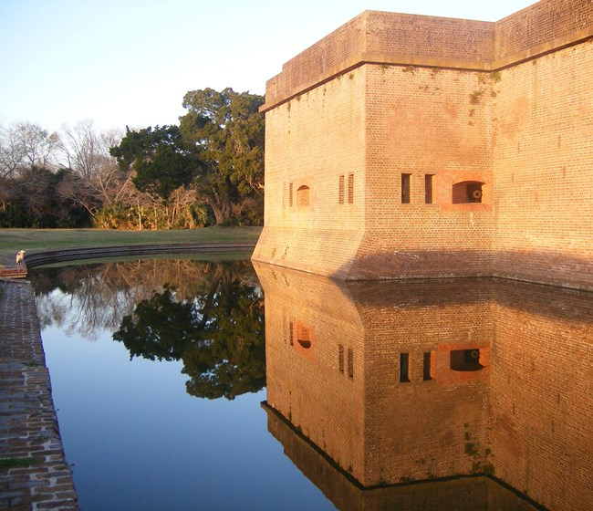 exterior masonry wall and water-filled moat