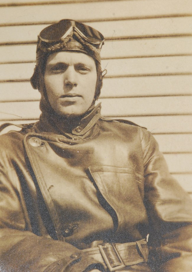 Black and white photo of man wearing leather jacket, cowl, and flight goggles.