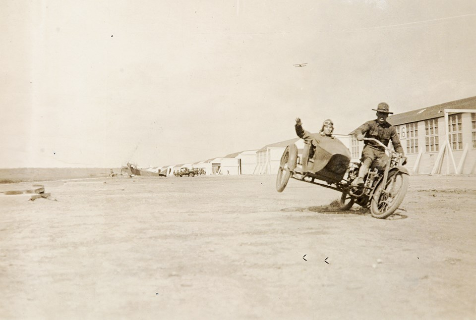 Black and white photo of man riding a motorcycle with another man in sidecar in front of airplane hangars.