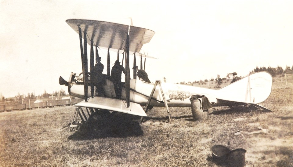 "Photo of landed biplane. Three men look inside cockpit. A dragon is painted on the fuselage, and the tail is marked with ""Northwest Aircraft Corporation Portland Oregon"""