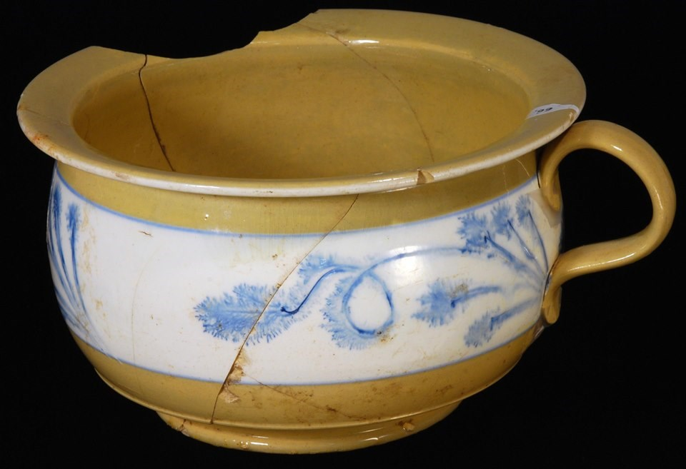Round chamber pot with handle. Yellow with a blue and white design around middle.