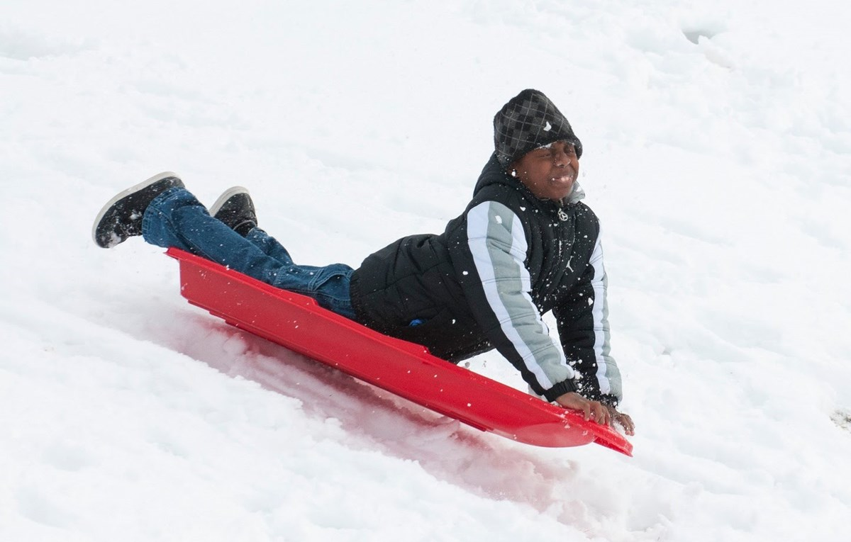 Child sledding down a hill in the snow