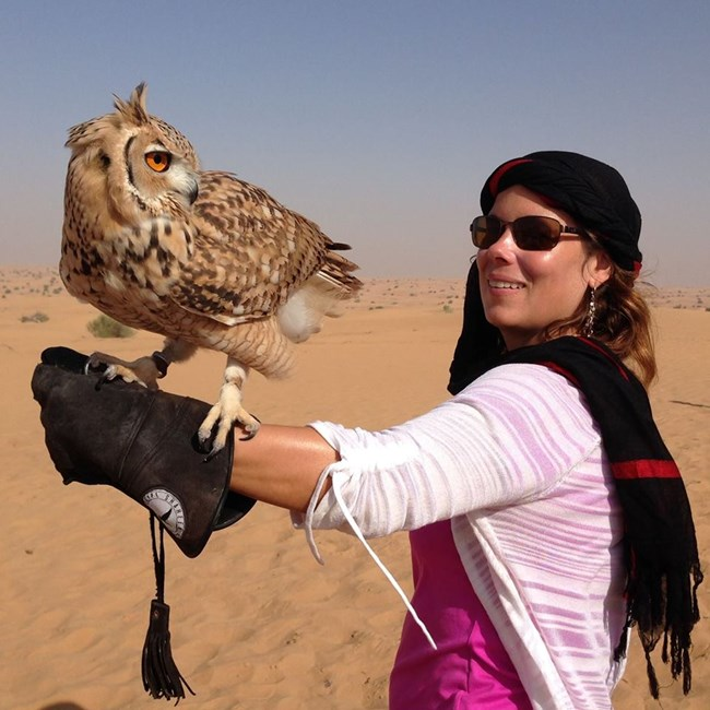 woman wearing scarf on head holding owl on outstretched gloved arm