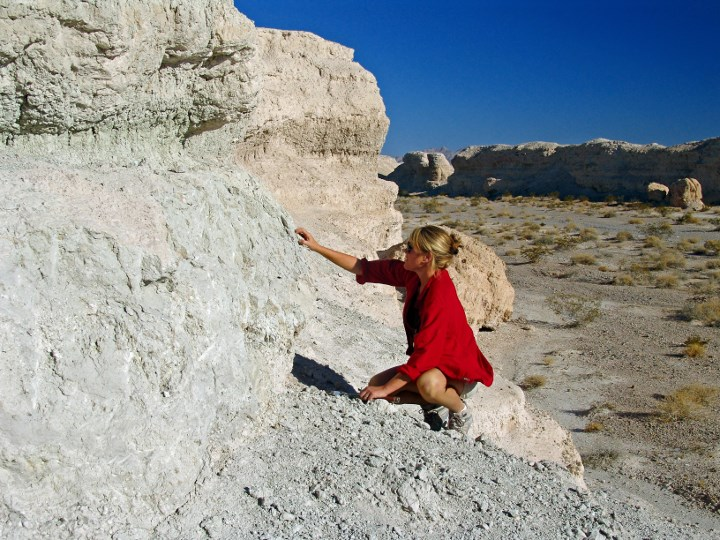 researcher examining a large rock
