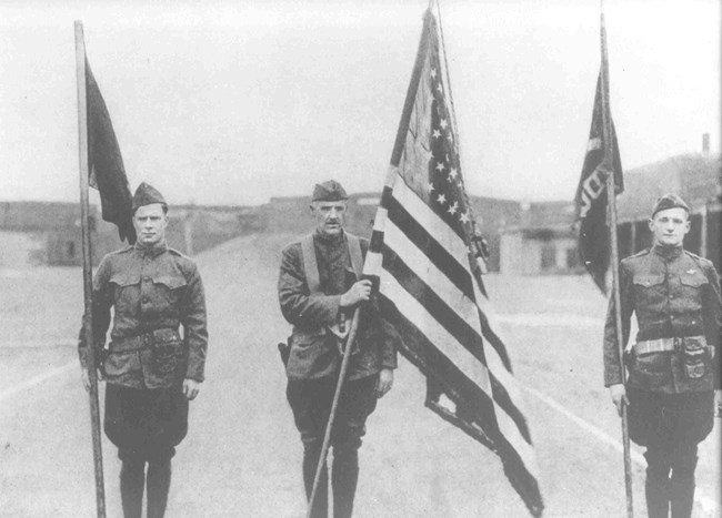 Three soldiers in World War I Uniforms holding flags