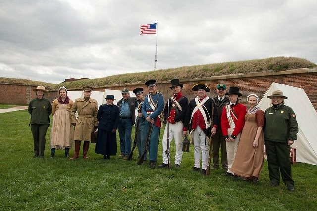 Three park rangers pose with volunteers in period costumes.