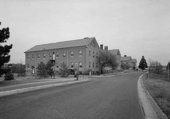 B&W photo of a brick building with a road running in front.