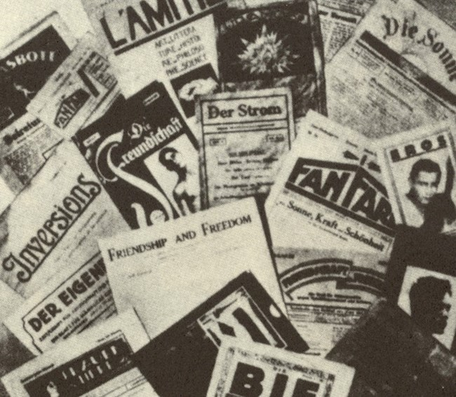 B&W photo of print periodicals with ink images and words piled together.