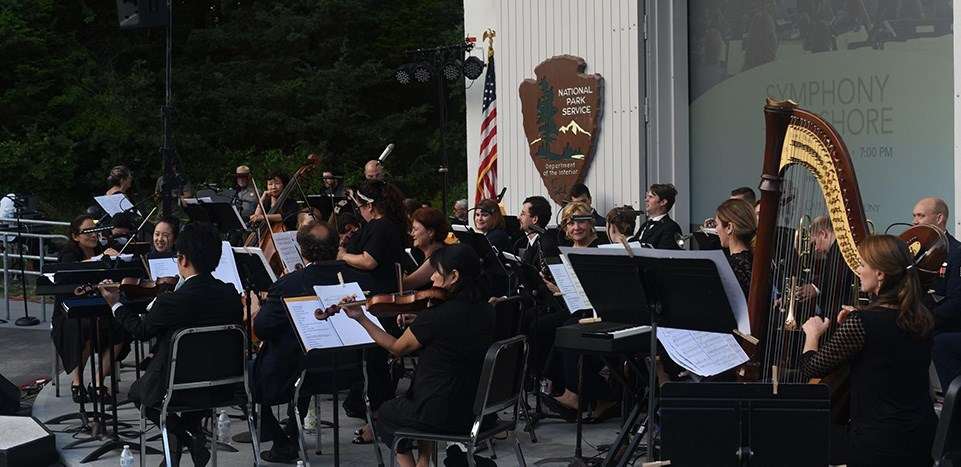 "A symphony performs outdoors in a white amphitheater. The projector screen behind them reads, ""Symphony at the Seashore."""