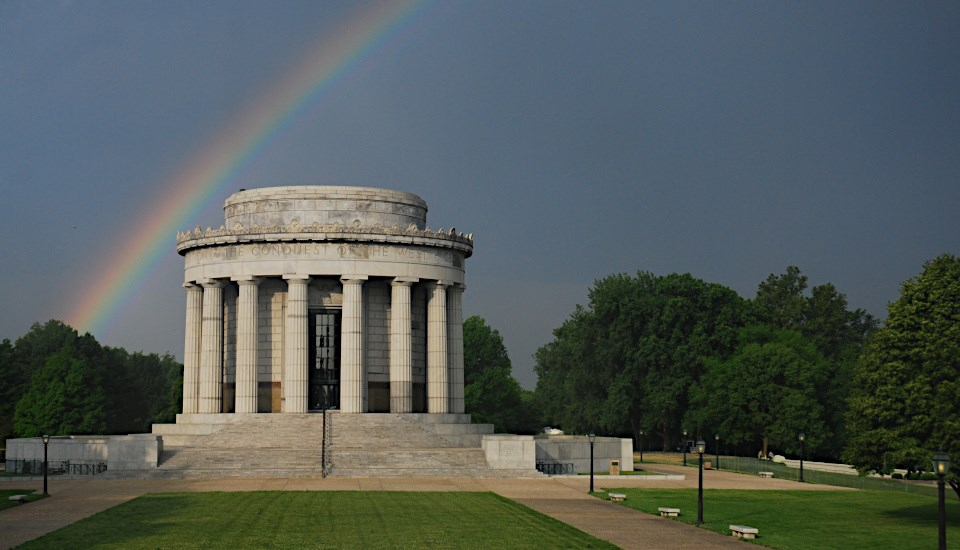 Memorial building in park setting with rainbow overhead