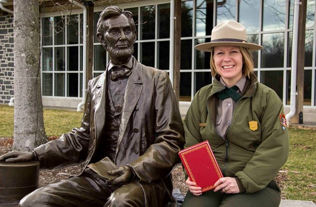 Barbara Sanders sitting next to a statue of Abraham Lincoln