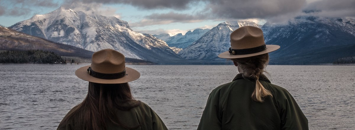 Back of two rangers in flat hats looking a lake in front of a mountain